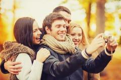 Groupe d'amis avec l'appareil-photo de photo en parc d'automne Photographie stock libre de droits