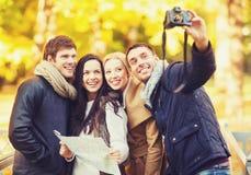 Groupe d'amis avec l'appareil-photo de photo en parc d'automne Photographie stock