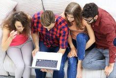 Groupe d'amis avec l'ordinateur portable se reposant sur le divan Photo stock