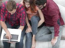 Groupe d'amis avec l'ordinateur portable se reposant sur le divan Image stock