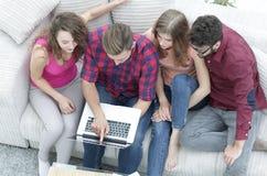 Groupe d'amis avec l'ordinateur portable se reposant sur le divan Photographie stock