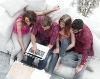 Groupe d'amis avec l'ordinateur portable se reposant sur le divan Photos stock