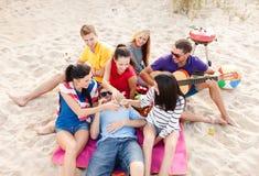 Groupe d'amis avec la guitare ayant l'amusement sur la plage Images libres de droits