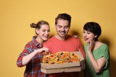 Groupe d'amis avec la pizza délicieuse Image libre de droits