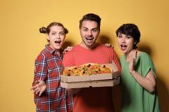 Groupe d'amis avec la pizza délicieuse Images stock