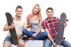 Groupe d'amis avec la planche à roulettes et la sucrerie Photos stock
