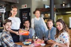 Groupe d'amis avec la serveuse dans le restaurant Photos libres de droits