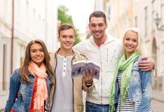 Groupe d'amis avec la ville l'explorant de guide de ville Photos stock
