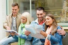 Groupe d'amis avec la ville l'explorant de guide et de carte Photographie stock libre de droits
