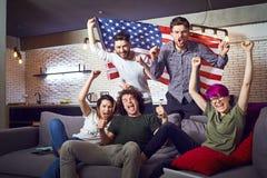 Groupe d'amis avec le drapeau américain à une partie Photographie stock libre de droits