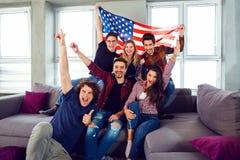 Groupe d'amis avec le drapeau américain à une partie Images stock