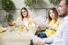 Groupe d'amis avec le menu de restaurant Photographie stock