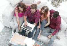 Groupe d'amis avec un ordinateur portable, discutant la vidéo Image libre de droits