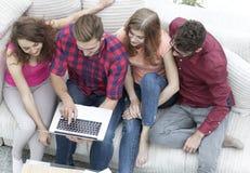 Groupe d'amis avec un ordinateur portable, discutant la vidéo Image stock