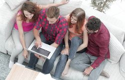 Groupe d'amis avec un ordinateur portable, discutant la vidéo Photo stock