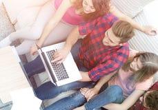 Groupe d'amis avec un ordinateur portable, discutant la vidéo Photographie stock