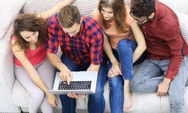 Groupe d'amis avec un ordinateur portable, discutant la vidéo Photos stock