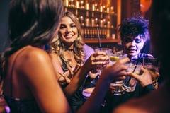 Groupe d'amis ayant des boissons à la boîte de nuit Photo stock