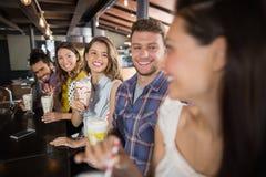 Groupe d'amis ayant des boissons dans le restaurant Images stock
