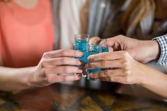 Groupe d'amis ayant des tirs de tequila dans la barre Images stock
