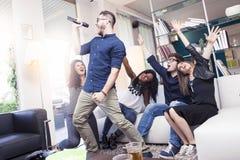 Groupe d'amis ayant l'amusement à la maison chantant une chanson ensemble Photos libres de droits