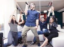 Groupe d'amis ayant l'amusement à la maison chantant une chanson ensemble Images libres de droits