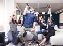 Groupe d'amis ayant l'amusement à la maison chantant une chanson ensemble Photographie stock