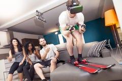 Groupe d'amis ayant l'amusement à la maison skiant utilisant la visionneuse Photos libres de droits