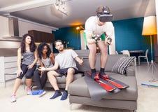 Groupe d'amis ayant l'amusement à la maison skiant utilisant la visionneuse Photo libre de droits
