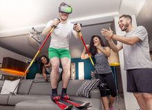 Groupe d'amis ayant l'amusement à la maison skiant utilisant la visionneuse pour le virt Photographie stock libre de droits