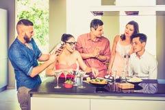 Groupe d'amis ayant l'amusement à la partie de maison avec pré l'aperi de dîner Photo stock