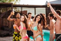 Groupe d'amis ayant l'amusement à la piscine dehors Images stock
