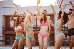 Groupe d'amis ayant l'amusement à la piscine dehors Photos stock
