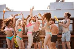 Groupe d'amis ayant l'amusement à la piscine dehors Photographie stock libre de droits