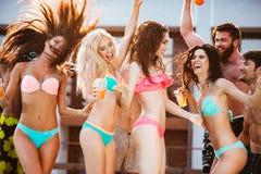 Groupe d'amis ayant l'amusement à la piscine dehors Photo stock