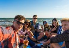 Groupe d'amis ayant l'amusement à la plage Image stock
