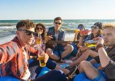 Groupe d'amis ayant l'amusement à la plage Photos stock