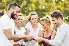 Groupe d'amis ayant l'amusement au festival de couleur Photos stock