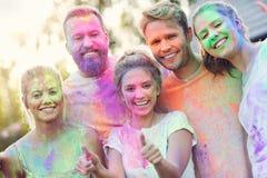 Groupe d'amis ayant l'amusement au festival de couleur Photo libre de droits