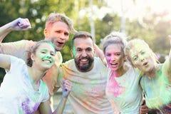 Groupe d'amis ayant l'amusement au festival de couleur Photographie stock libre de droits