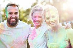 Groupe d'amis ayant l'amusement au festival de couleur Image stock