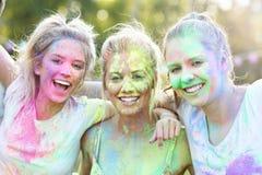 Groupe d'amis ayant l'amusement au festival de couleur Photographie stock