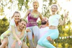 Groupe d'amis ayant l'amusement au festival de couleur Photo stock