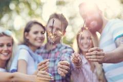 Groupe d'amis ayant l'amusement avec des cierges magiques Photographie stock libre de droits