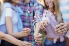 Groupe d'amis ayant l'amusement avec des cierges magiques Photos libres de droits