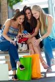 Groupe d'amis ayant l'amusement avec des smartphones Photo libre de droits