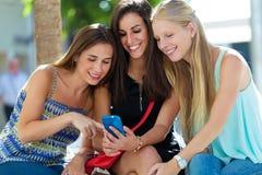 Groupe d'amis ayant l'amusement avec des smartphones Images stock