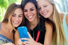 Groupe d'amis ayant l'amusement avec des smartphones Photos stock