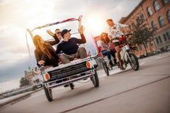 Groupe d'amis ayant l'amusement avec deux tricycles sur la route Photo stock