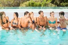 Groupe d'amis ayant l'amusement dans la piscine Images libres de droits